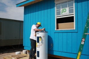 Bob puts the finishing touches on a new water heater (in this climate, you can keep them outdoors).