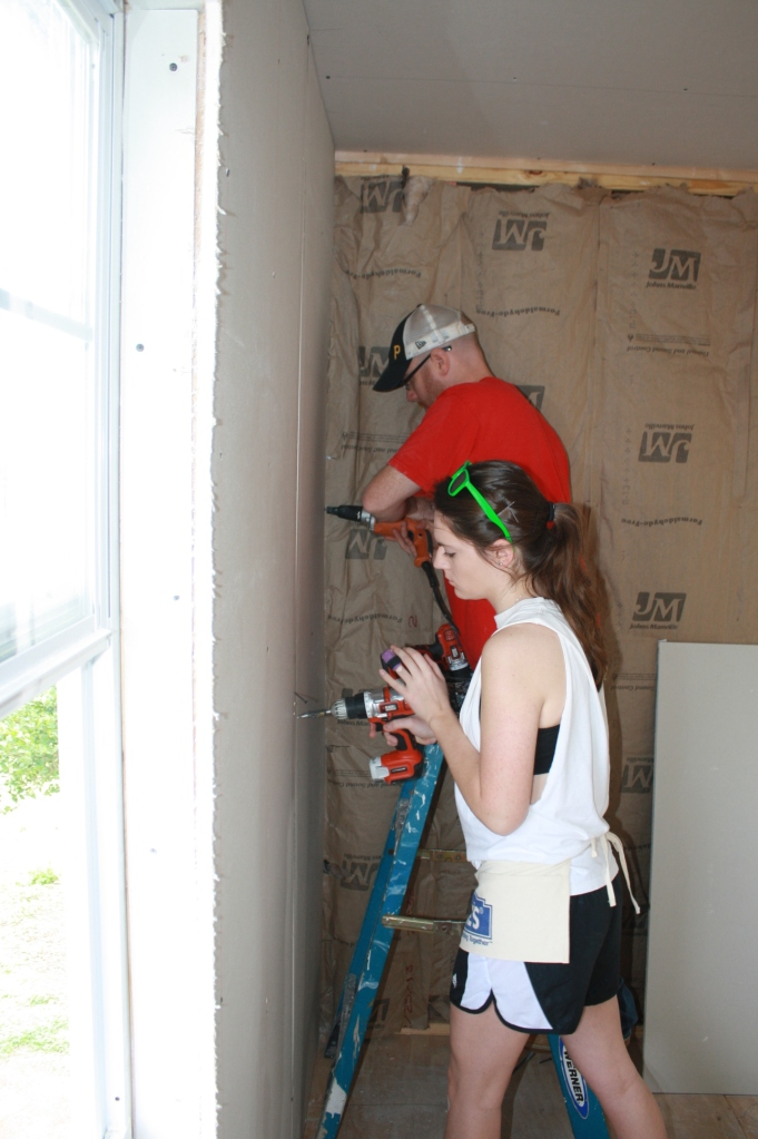 Marla and Joe work on installing one of the final pieces of drywall - we finished hanging all the board today!