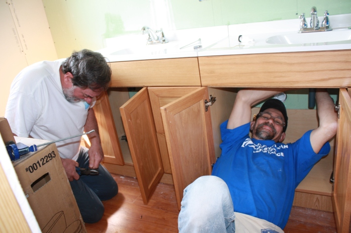 Gabe and Bob work on installing the fixtures in the new bathroom!