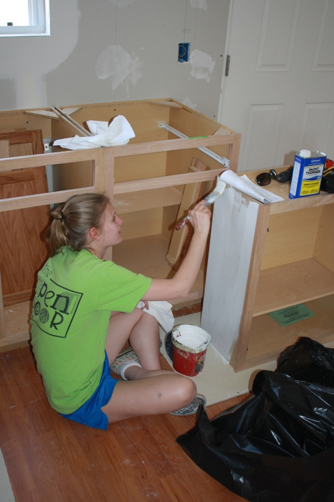 Lindsay helps prepare the kitchen cabinets for their final installation.
