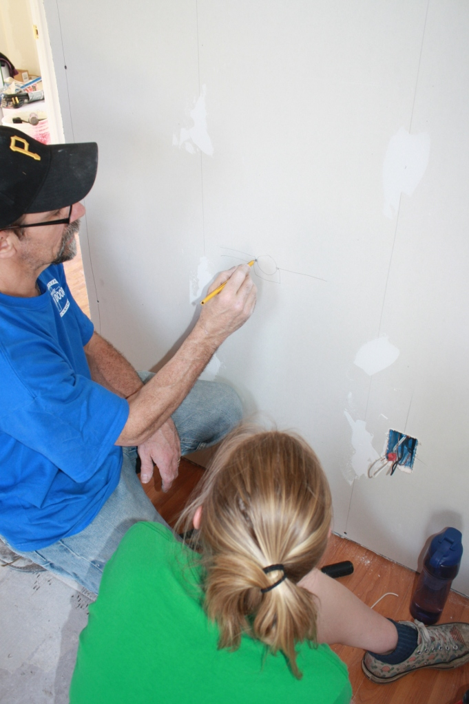 Lindsay gets another tutorial from the electrical guru, complete with visual aids on the wall.