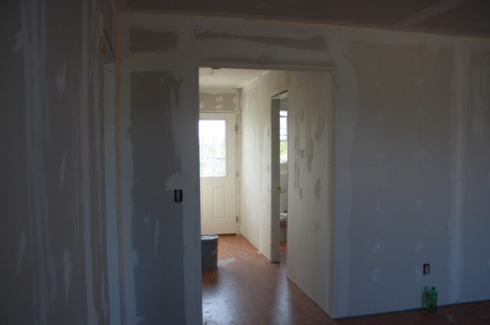 The hallway to the back door, the bath, and the rear bedroom.