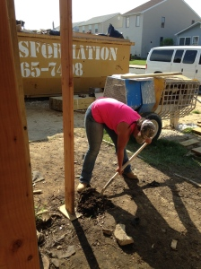 Alexis digging a hole for the footer for the deck.
