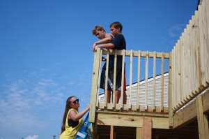 Caleb, Joe, and Katie moving the railing toward completion.