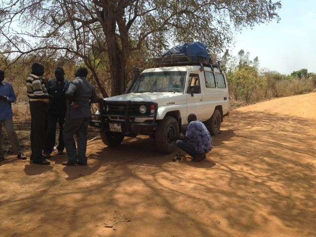 The roads were hard on us and our equipment.  The 23 of us traveled in three vehicles like this.  Here, we experience a minor delay for a tire change.