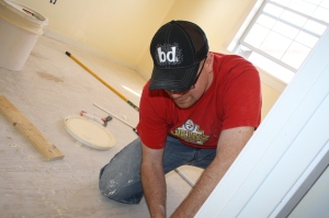 Joe finishes installing the baseboard.