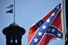 The South Carolina and American flags flying at half-staff behind the Confederate flag erected in front of the State Congress building in Columbia, South Carolina on June 19, 2015. Police captured the white suspect in a gun massacre at one of the oldest black churches in Charleston in the United States, the latest deadly assault to feed simmering racial tensions. Police detained 21-year-old Dylann Roof, shown wearing the flags of defunct white supremacist regimes in pictures taken from social media, after nine churchgoers were shot dead during bible study on Wednesday. AFP PHOTO/MLADEN ANTONOV        (Photo credit should read MLADEN ANTONOV/AFP/Getty Images)