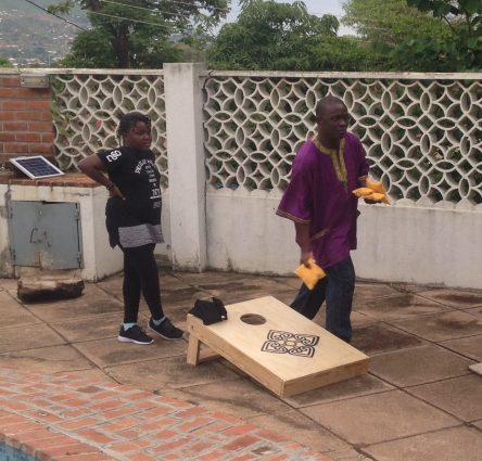 Davies and his daughter Chikondi try out the custom-made corn hole game we brought as a thank-you gift.