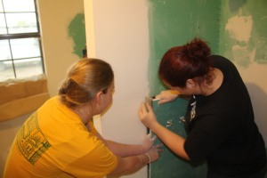 Lindsay and Kati are fitting in a piece of drywall that was inexplicably missing...