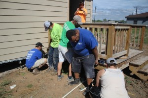 The team works together to raise the decking onto a termite-resistant surface.
