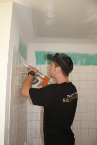 Joe is sealing up the bathroom tile.